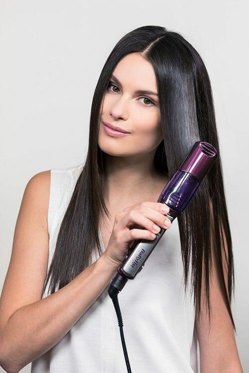 femme qui se lisse les cheveux avec un lisseur vapeur babyliss